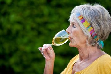 ältere frau trinkt weißwein