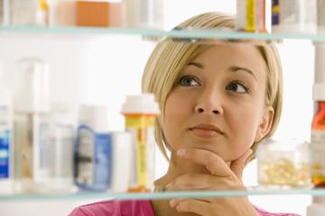Woman Looking in Medicine Cabinet