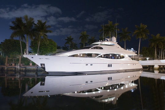 night shot of luxury yacht docked by the house in canal palm trees and moon light