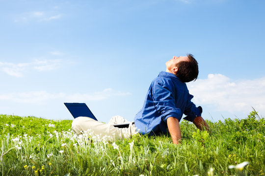 \Man working with laptop in a meadow of flowers with copyspace