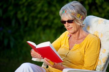 ältere dame liest im garten
