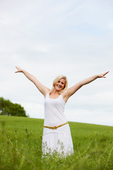 Young woman in field arms outstretched with joy