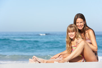 Mother And Daughter Relaxing Together On Beach Holiday