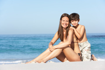 Mother And Son Relaxing Together On Beach Holiday