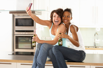 Two Girlfriends Taking Photo With Digital Camera In Modern Kitch