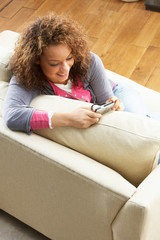 Woman Looking At Pictures On Digital Camera Relaxing Sitting On