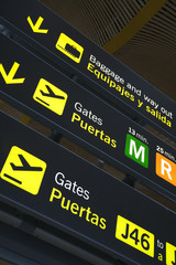 Airport departure gate sign written in English and Spanish