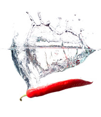 red hot paprika splashing into water isolated on white