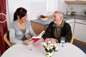 Frau liest Senioren aus einem Buch vor.