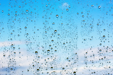 Water droplets on glass against the blue sky with clouds