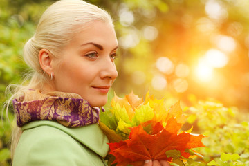 Wall Mural - Beautiful blond woman in park with autumn leaves