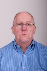 Older Balding Man in Blue Shirt Holding Chin Up Looking Through