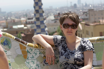 Girl sits on bench at park Guell
