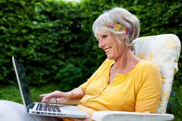 seniorin mit laptop im garten