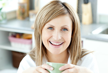 Cheerful woman holding a cup of tea in the kitchen