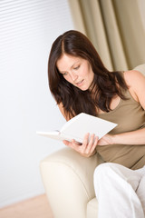 Young woman read book relaxing on sofa