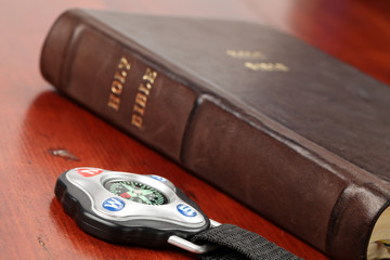Compass and the Holy Bible in background