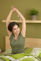 Smiling woman waking up stretching