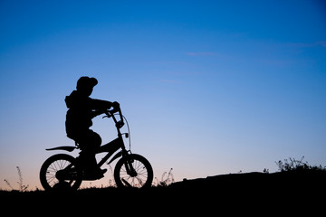Silhouette of boy on bike