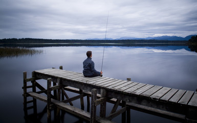 Fisherman sitting on a wooden jetty on a moody winters day