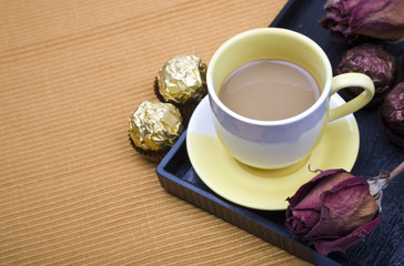 Coffee with chocolate candy and dried roses