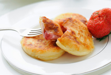 Curd pancakes with berries inside.