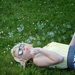 Girl Blowing Bubbles in Grass