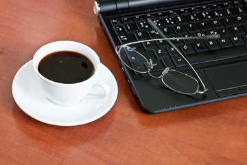 cup of coffee with a laptop and glasses