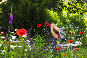 garden bench with straw hat within summer flowers 02