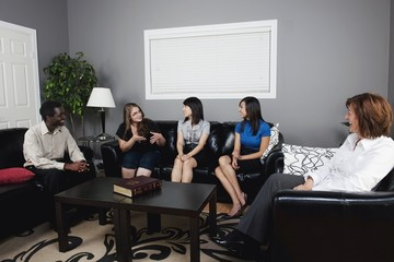 A Group Of People Talking In A Living Room