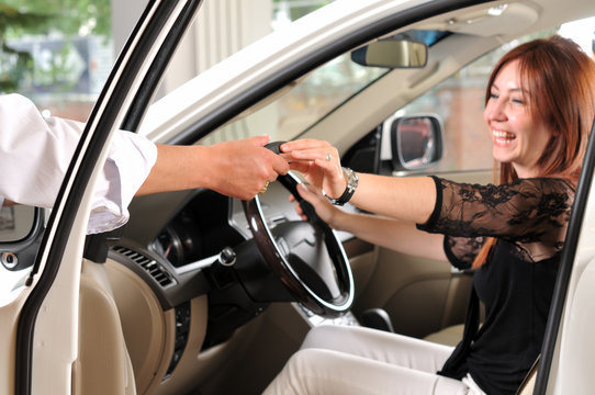 Car dealer giving keys of the new car to happy customer.