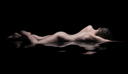 Nude woman lies in water, low key