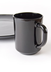 black ceramic cup of coffee and tea on background of plate