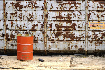 Orange barrel next to weathered dumpster