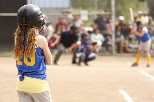 First base coach watching teammate up to bat