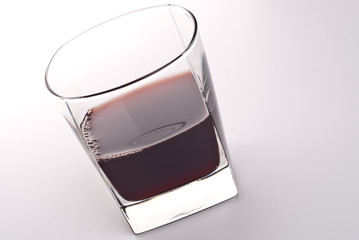 Glass of red drink isolated over white background