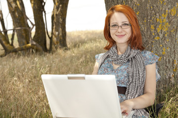 Young smiling fashion girl in glasses and notebook near tree.