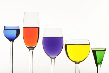 Five multi-coloured wine-glasses on white background