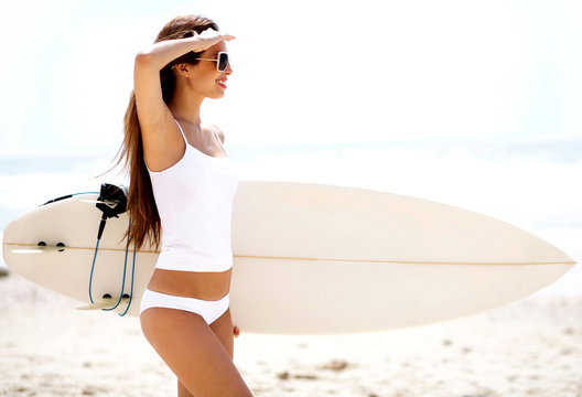 Young woman with surfboard and shielding eyes