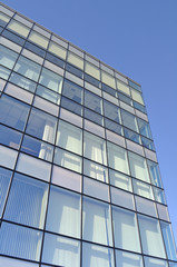 Facade of a modern office building made from blue glass.