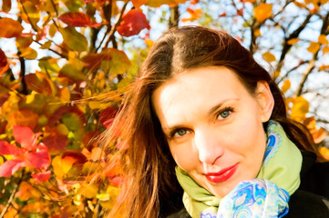 portrait of young smiling woman in autumn park
