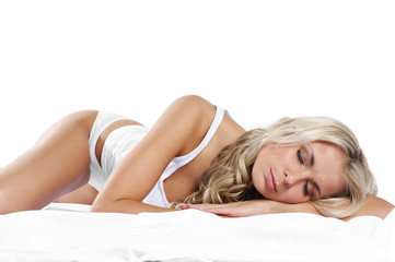 A young and attractive blond girl is lying on a white blanket