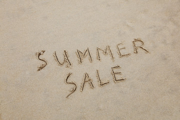 """Summer Sale"" written in the sand at the beach.  Sales concept"