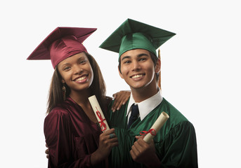 multi racial couple in cap, gown with diploma at graduation