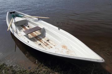Boat with oar on water beside coast