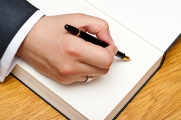 man signing a blank page of a book