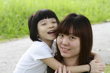An Asian daughter hugging her mother
