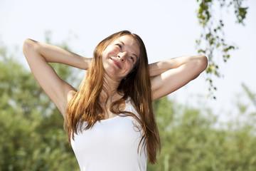 lächelnde hübsche junge Frau posiert mit Armen hinter dem Kopf