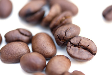 closeup of brown roasted coffee beans isolated over white