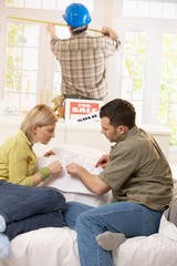 Couple looking at ground plan of new house
